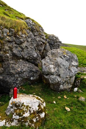 reuseable: Reuseable red aluminium drinking bottle on rocks in Peak District National Park