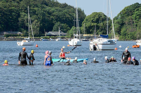 Pooley Bridge, England - July 7th, 2013  Unidentified people competing in open water swimming in Ullswater Lake Stock Photo - 22585854