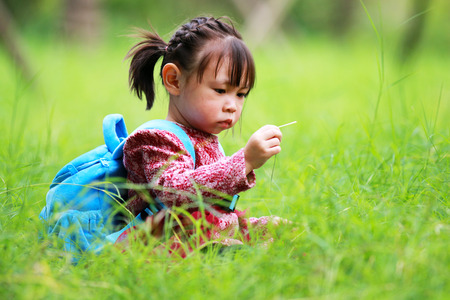Cute little girl sitting on the grass and playing 免版税图像