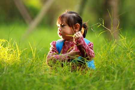 Little girl sitting on the grass and playing