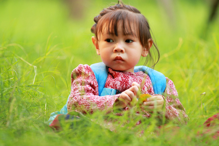 Little girl sitting on the grass staring at the camera Stock Photo