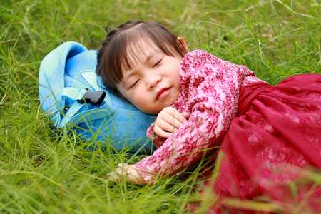 Cute little girl lying on the grass and slumbering