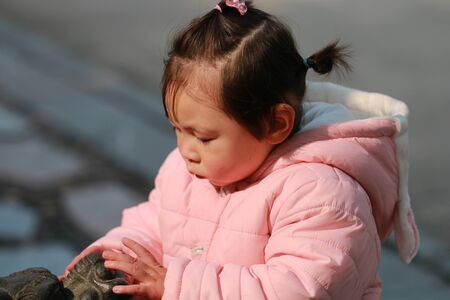 Little girl stroking an animal statue