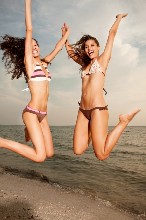 Happy excited young women in bikini jumping on beach photo