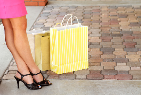Woman legs and shoes with shopping bags relaxing outdoors photo