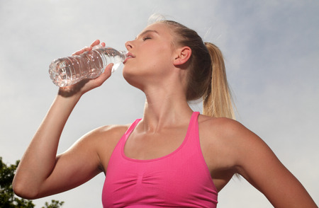 non moving activity: Portrait of young blonde fitness runner drinking out of water bottle