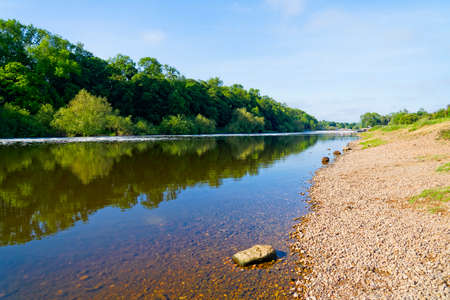 Standing on the pebble strewn banks of the clear, calm, River Trent on a bright spring morning near Gunthorpe weir