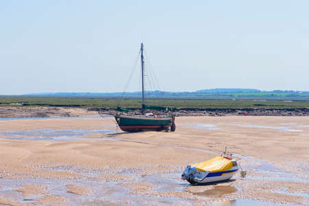 A old yacht and a motorboat are beached on a sandbank in an estuary at low tide. Salt marches stretch out in to the distance.