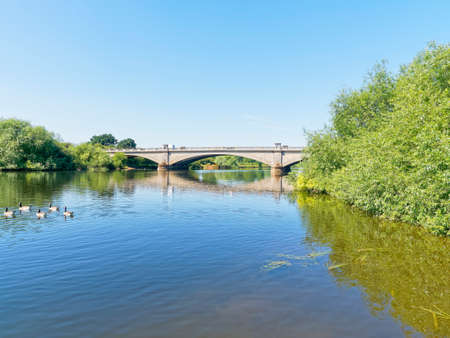 A calm River Trent flows under Gunthorpe Bridge on a bright, cloudless, summer day.