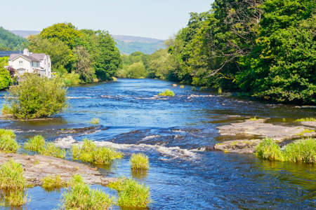 The River Dee flows fast between densley wooded banks on a bright summers day in Llangollen, Wales Banque d'images