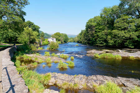 A low wall follows the curve of the fast flowing River Dee on a bright summer day in Llangollen, Wales Banque d'images