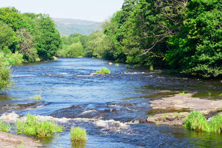 On a bright, hazy, summer day in Llangollen the River Dee flows fast over rocks creating small rapids. Banque d'images