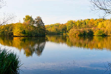 Early morning sun lights up the autumn foliage around the banks of a still lake.