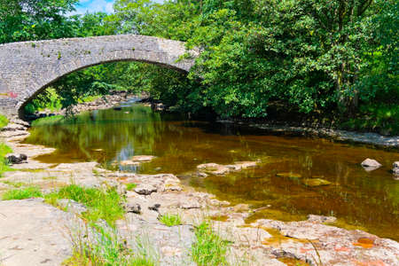 Peaceful summer day watching the clear water of the River Ribble flow under an old stone bridge near Stainforth. 版權商用圖片