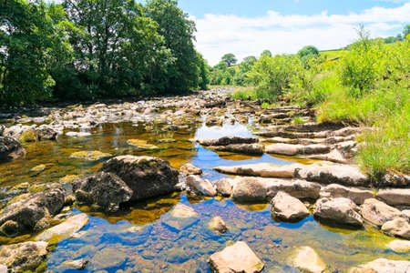 The crystal clear water of the rock strewn River Ribble on a summer day near Little Stainforth in the Yorkshire Dales