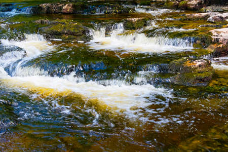 The clear water of the River Ribble becomes blurred as it passes over rocks near Stainforth in the Yorkshire Dales