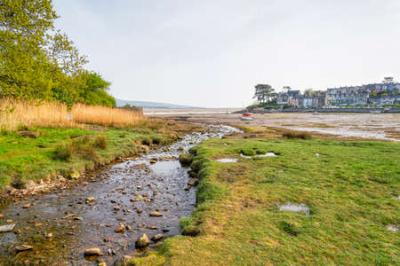 A stream runs down a small harbour near Portmadog at low tide. Small yachts sit on the sandy harobour floor.