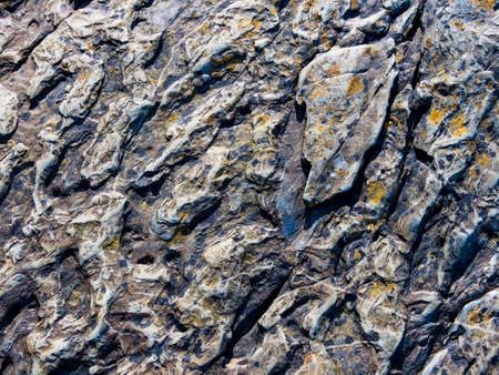 Close up of Welsh slate, with patches of orange and yellow lichen, worn smooth by the waters of the River Dwyryd Stockfoto