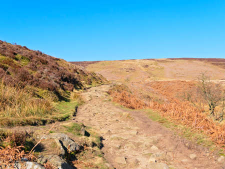 A rocky footpath winds up hill from Cutthroat Bridge to Derwent Moor in the Hope Valley, Derbyshire.