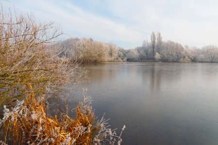 Bright winter sunshine starts to warm a frost covered landscape surrounding a frozen lake 免版税图像