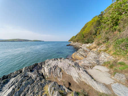 Steep rocky shores line the wide rippled waters of the River Dwyryd estuary on a bright spring day in Gwynedd, Wales