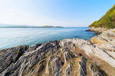 Erroded rocks line the shore of the River Dwyryd estuary under a blue hazy spring sky. Stockfoto