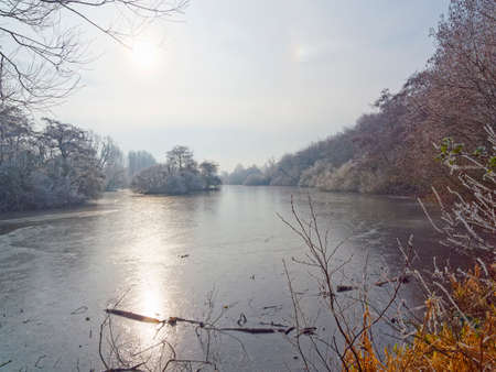 The low winter sun reflects off the icy surface of a shallow frozen lake on a cold and frosty morning