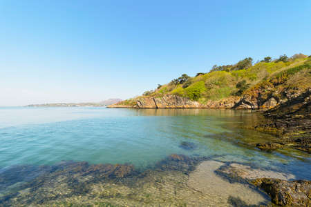 The crystal clear water of the River Dwyryd fills a small cove lined with slate cliffs on a bright spring day