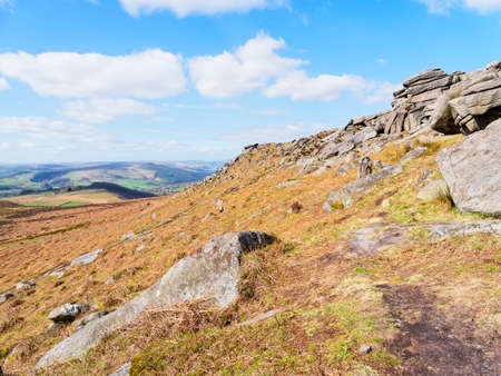 The ridge line of Higger Tor points across the Derbyshire Peak District on a bright spring day