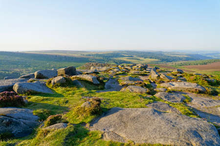 A hazy summer morning on the gritstone strewn Higger Tor in the Derbyshire Peak District 版權商用圖片