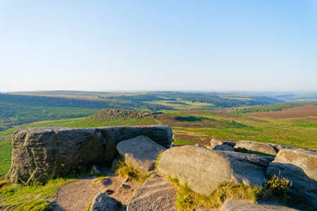 Over large gritstone boulders on top of Higger Tor to the ancient Carl Wark Hillfort on a hazy morning