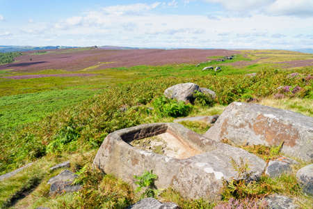 Ancient carved gritstone trough among the rocks and boulders on Hathersage Moor in Derbyshire