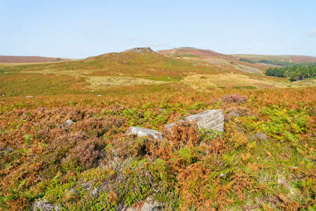Over gritstone boulders, bracken and heather to a distant misty Carl Wark fort on an autumn day in Derbyshire 写真素材