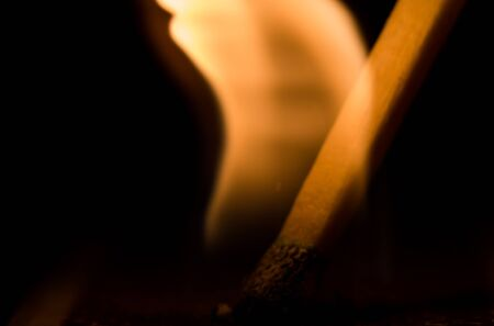 incendiary: Macro shot of lit match shows flame coming from head of match Stock Photo