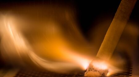 firestorm: Macro shot of lit match shows flame coming from head of match Stock Photo