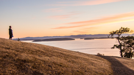 puget sound: Woman stares out into islands at the San Juan Islands at sunset Stock Photo