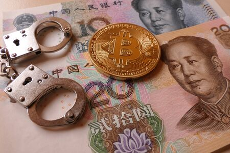 An golden Bitcoin, an virtual currency in physical coin form, displayed with handcuffs and Chinese Yuan, symbolic illustration for the restriction of Bitcoin in China