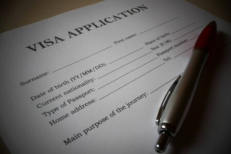 Visa application form with a pen for filling out. Document For applying to enter in a foreign country. Фото со стока
