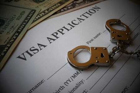 Visa application form with some US-Dollar Notes and handcuffs, Illustration for misuse and corruption of Visa forms