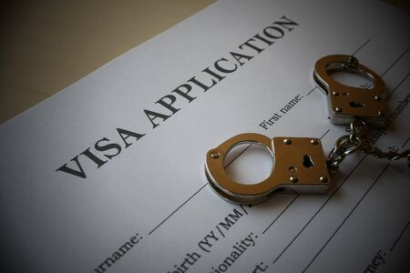 Visa application form with handcuffs, Illustration for misuse of fake Visa