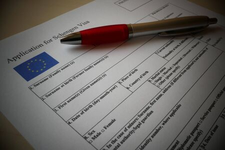 EU Schengen Visa application form with a pen for filling out. Document For applying to entry in the European Union. Фото со стока