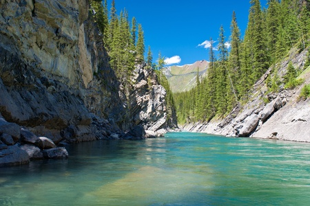the turquoise waters of the cascade river, flows  through a rugged canyon, in banff national park. photo