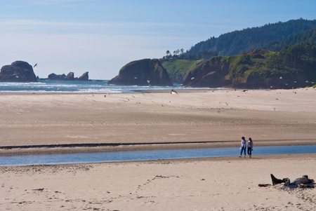 two woman having a peaceful walk on the beach, at cannon beach, oregon. photo