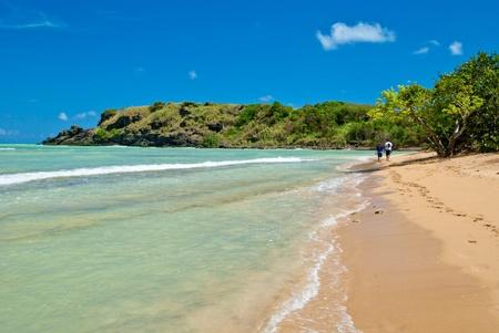 a couple walks along hidden beach, on the north shore of puerto rico.