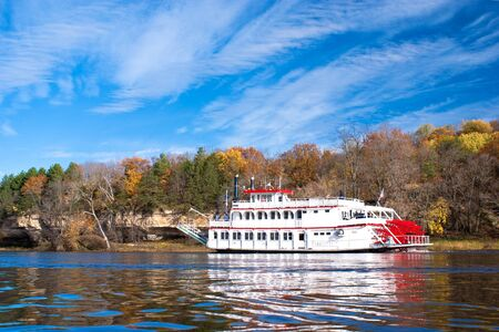 a paddleboat, travels up along the sandstone cliff shoreline, of the st. croix river, wisconsin.