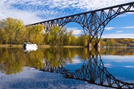 forest railroad: railroad bridge reflections, on the tranquil waters of the st. crois river, wisconsin. Stock Photo