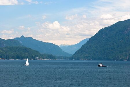 bc: sailboat and tugboat, on the pacific waters of the inside passage, british columbia, canada Stock Photo