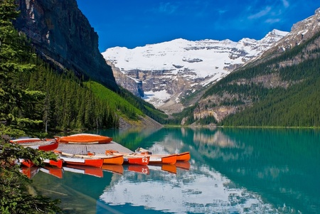 On the Placid turquise waters of Lake Louise, canoes waiting for canoeist, in Banff National Park.