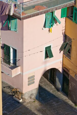 italian village: mainstreet in riomaggiore, is an old cobblestone street which splits to go down through the heart of the village, to a marina on the mediterranean, or up through the base of a house, to a hilltop where a castle is located, overlooking the mediterranean. i Stock Photo