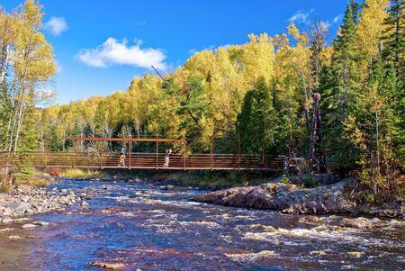 minnesota woods: hiking over the baptism river, on an iron bridge, autumn, tettegouche state park, minnesota.